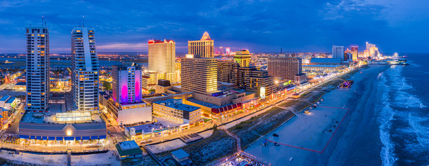 Fotomurales - Aerial panorama of Atlantic city along the boardwalk at dusk. In the 1980s, Atlantic City achieved nationwide attention as a gambling resort and currently has nine large casinos.