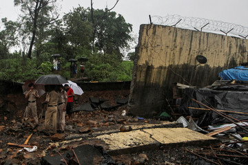 Police personnel stand among the debris after a wall collapsed on hutments due to heavy rains in Mumbai
