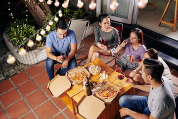 Friends drinking wine, eating snacks and discussing latest news at backyard party