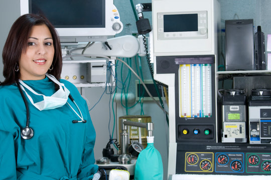Hispanic Woman Surgeon in front of Anesthesiology Equipment