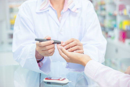 Hands of Pharmacist  checking patient blood sugar by glucometer in drugstore