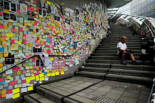 A man sits on the stairs of the Legislative Council as he reads post-it notes left behind by protesters, a day after they broke into the building, in Hong Kong