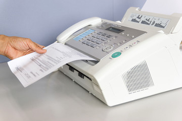 hand man are using a fax machine in the office