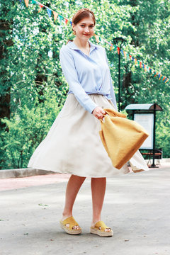 Summer fashion outfit. Girl in dress, yellow shoes and trendy knitted bag