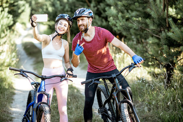 Young sports couple taking selfie photo with smartphone while riding mountain bicycles on the...