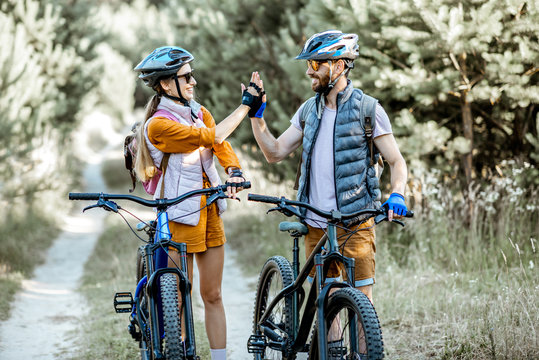 Young and active couple giving a five each other, having fun while traveling with bicycles on the forest road