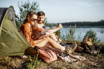 Young and cheerful couple having a picnic at the campsite while traveling in the forest near the lake during the sunset