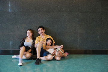full shot group of happiness asian family father, mother, son and daughter taking picture in sitting pose after playing basketball in sport club with happy smiling face during holiday vacation