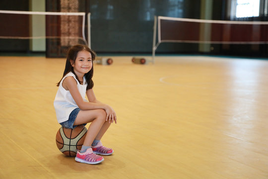 full shot of happy asian daughter taking a break and sitting on basketball in sport club with happy smiling face during holiday vacation