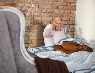 Woman talking on mobilephone in bed