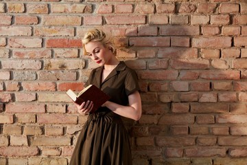 Young woman reading book over brick wall