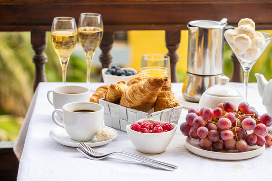 Luxury brunch on the hotel  terrace, coffee maker, teapot, cups, croissants, fruits, orange juice and champagne. Good morning scenery background.
