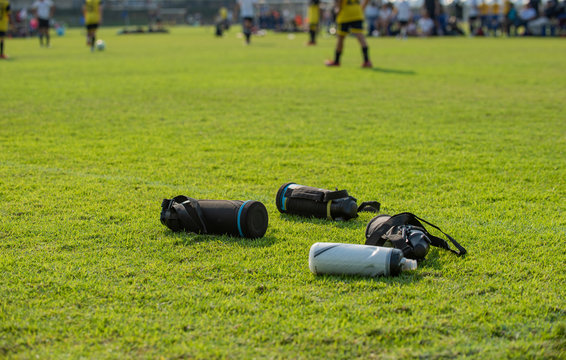 Sport plastic bottles of fresh water left on a football field while players having a match on a pitch as seen in a background.