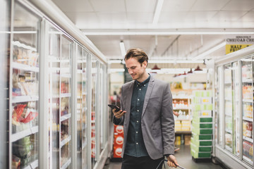 Man looking at smartphone in a grocery store