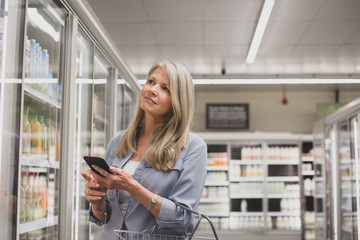 Mature woman looking at smartphone in a grocery store