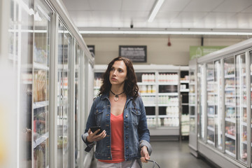Young adult female with smartphone in a grocery store