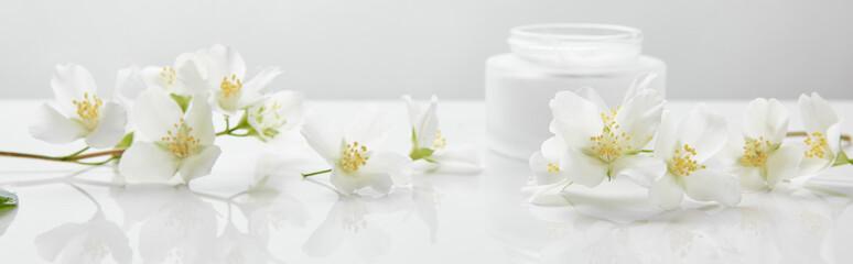 Spoed Fotobehang Bloemen panoramic shot of jasmine flowers on white surface near jar with cream