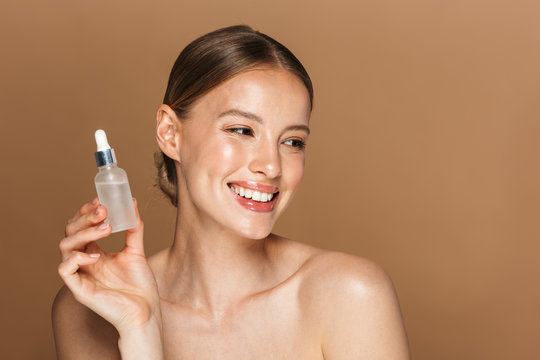 Smiling happy young amazing woman posing isolated over brown chocolate background wall holding oil drop serum.
