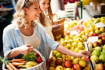 Young woman shopping healthy food on the market Wall mural