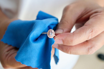 Jeweller hand polishing and cleaning jewelry diamond ring with micro fiber fabric