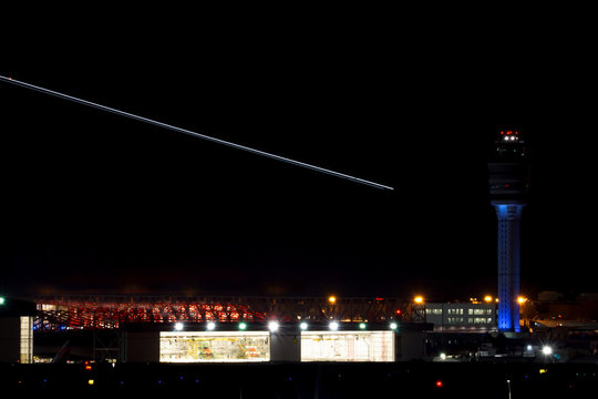 nightime view of the Atlanta international airport with air traffic control and streaks of planes taking off over bright hangars