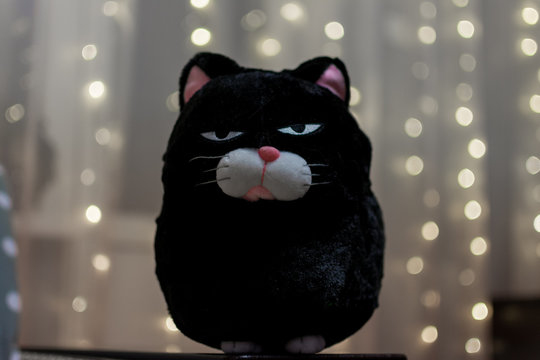 Soft toy cat with an angry expression on his face on the background of blurred garland