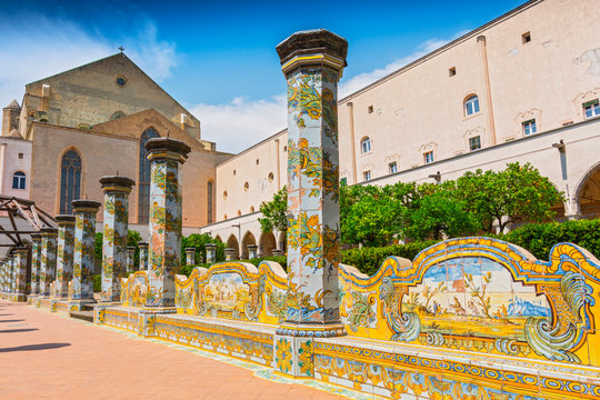 Sunny cloister of the Clarisses decorated with majolica tiles from Santa Chiara Monastery in Naples, Italy.