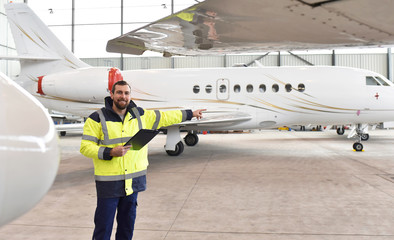 Airport workers check an aircraft for safety in a hangar Fototapete