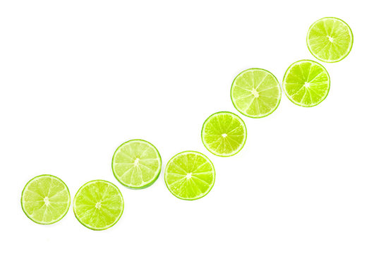 Many vibrant lime slices, shot from the top on a white background in a flat lay composition