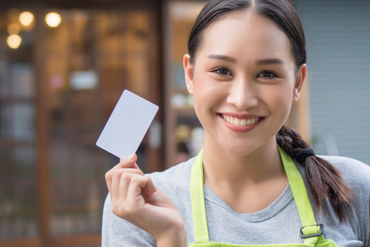 asian woman business owner showing blank credit card