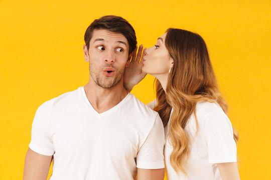 Portrait of joyful woman whispering secret or interesting gossip to excited man in his ear