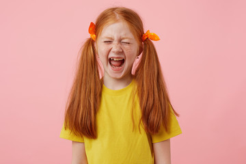 Portrait of screaming petite freckles red-haired girl takes his two tails, wears in yellow t-shirt, looks sad, stands over pink background.