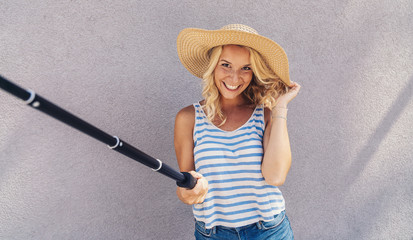 Young girl smiling and use selfie stick to take a selfie, on summer in city street. Urban life concept.