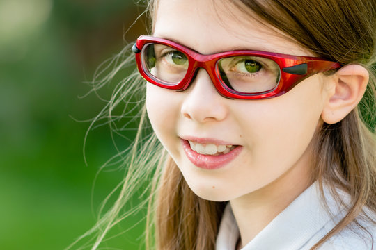 Close-up portrait of a girl child wearing red prescription sports glasses or goggles