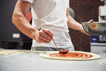 Close up view of baker putting sauce to make delicious pizza for an order in restaurant