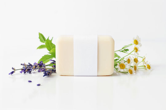 Closeup of hand made herbal soap bar in blank paper label package. Mint leaves, lavender and feverfew flowers on white table backround. Spa concept. Skin product mockup scene. Cosmetic product.