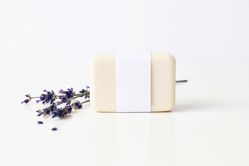 Closeup of hand made herbal soap bar in blank paper label package and bunch of lavender flowers on white table backround. Spa concept. Skin product mockup scene. Cosmetic product.