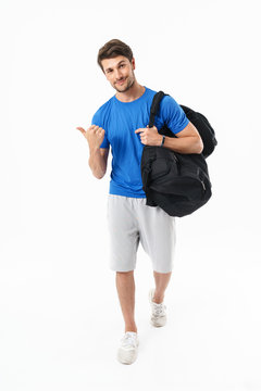 Pleased optimistic handsome young sports fitness man standing isolated over white wall background holding bag pointing to copyspace.