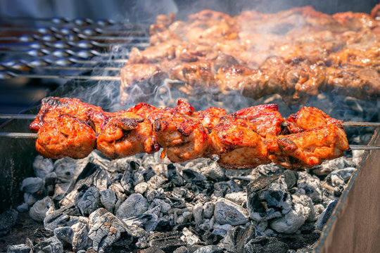 fresh hot grilled chicken shish kebab barbecue on grid over coal with smoke. Close-up