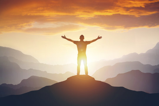Man standing on edge of mountain feeling victorious with arms up in the air.