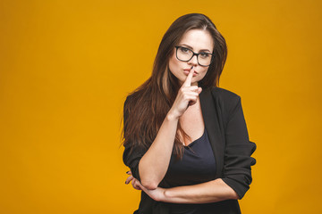 Closeup of businesswoman with finger on lips isolated over yellow background.