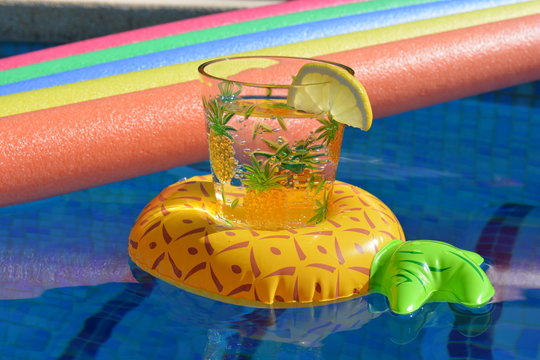 Cocktail or Glass of water,  in an inflatable pineapple drinks holder and pool noodles floating in a swimming pool. Summer vibes, bright and colourful, keeping cool