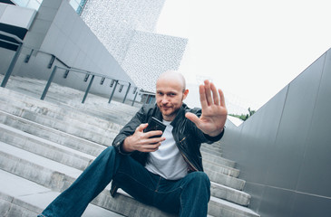 Adult bald bearded smiling man with mobile sitting in stair closing camera by hand, no more photo