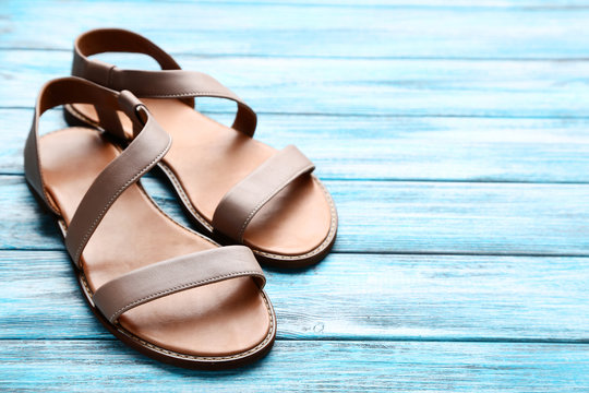 Female beige sandals on blue wooden table