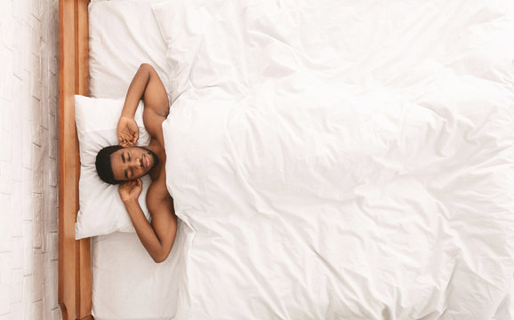 Naked african-american man sleeping in bed top view