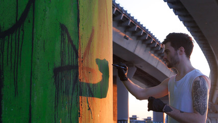A man standing near the wall with graffiti - holding a marker