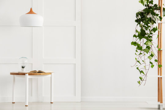 Modern white corridor with simple table and lamp