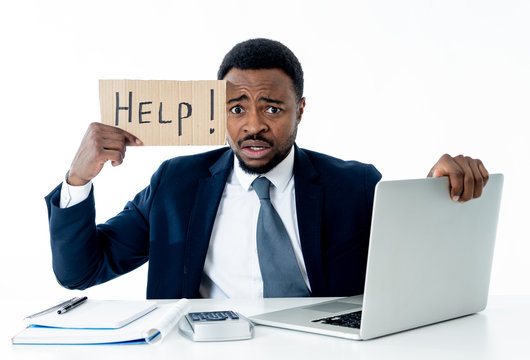 Depressed sad and frustrated young businessman holding a help sign in stress at workplace