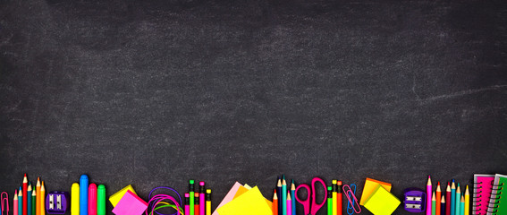 School supplies bottom border banner. Top view on a chalkboard background with copy space. Back to school concept.