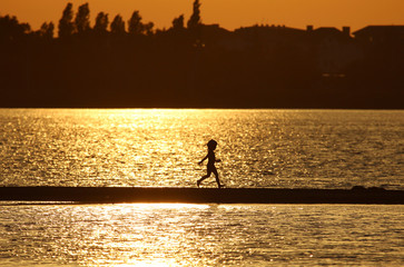 A child runs along a sand bar amidst the waters of Lake Moynaki during sunset in Yevpatoriya